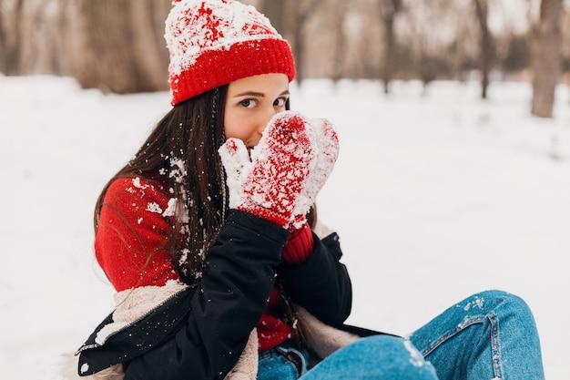 Jovem, muito sorridente, feliz, usando luvas vermelhas e chapéu de malha, vestindo um casaco de inverno, caminhando no parque, brincando com a neve em roupas quentes, aquecendo as mãos