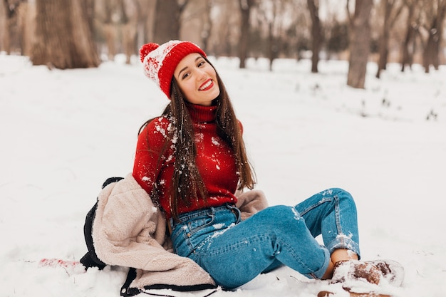 Jovem, muito sorridente, feliz, usando luvas vermelhas e chapéu de malha, vestindo um casaco de inverno, caminhando no parque, brincando com a neve em roupas quentes