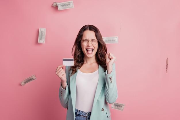 Jovem, muito sorridente, mostrando o cartão de crédito, gritando, humor animado, ganhe o jackpot na parede rosa
