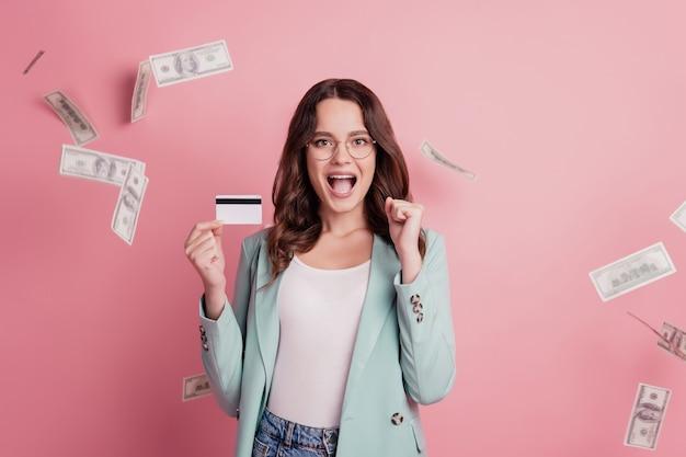 Jovem, muito sorridente, mostrando o cartão de crédito, levantar o punho e gritar, alegre-se com o dinheiro cair fundo rosa