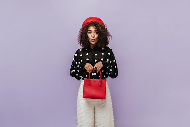 Jovem mulata tímida com cabelo fofo e boné vermelho, blusa preta de bolinhas e calça branca estilosa olhando para a câmera