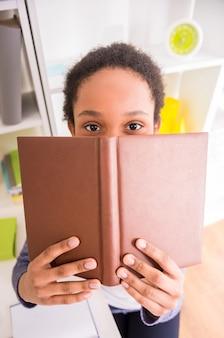 Jovem mulato bonito está segurando um livro nas mãos.