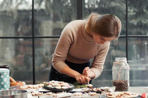 Jovem mulher a decorar pastelaria na cozinha