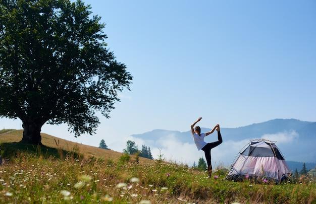 Jovem mulher a descansar perto da barraca do turista pela manhã de verão nas montanhas