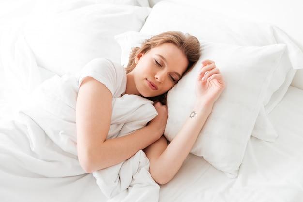 Jovem mulher a dormir situa-se na cama com os olhos fechados.
