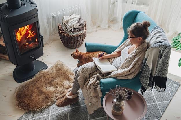 Jovem mulher a escrever num caderno, sentada numa poltrona junto à lareira com um gato doméstico