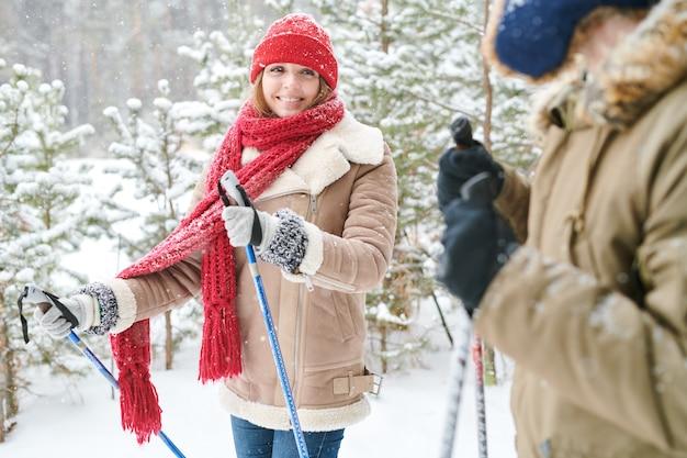 Jovem mulher a esquiar na floresta a sorrir
