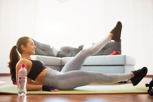Jovem mulher a fazer exercícios de esporte no quarto durante a quarentena. alegre garota positiva fazendo exercício de pernas de tesoura e sorrindo