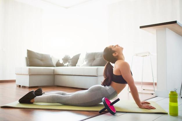 Jovem mulher a fazer exercícios de esporte no quarto durante a quarentena. alongamento no tapete de ioga. deitado de bruços e alongando-se.