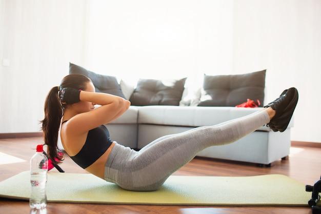 Jovem mulher a fazer exercícios de esporte no quarto durante a quarentena. garota bem construída, fazendo exercícios abdominais na esteira do chão. mantenha as mãos perto da cabeça. segure as partes superior e inferior do corpo no ar.
