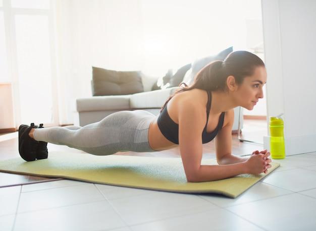Jovem mulher a fazer exercícios de esporte no quarto durante a quarentena. vista lateral da garota ficar na posição de prancha usando a parte do corpo do antebraço em ambas as mãos. corpo reto e bem construído.