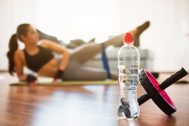Jovem mulher a fazer exercícios de esporte no quarto. garrafa de água e rolo de exercício abdominal na frente. garota de alongamento e treinamento com resistência banda sozinha no quarto.