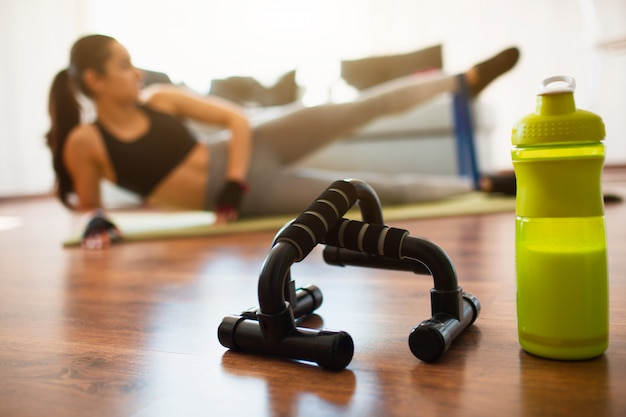 Jovem mulher a fazer exercícios de esporte no quarto. garrafa de proteína verde e barra de mão de flexões na frente. garota exercitando usando banda de resistência. estique a perna esquerda para cima e para frente.