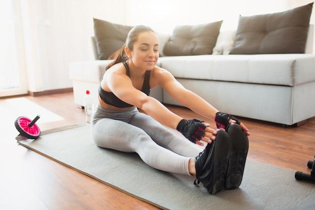 Jovem mulher a fazer exercícios de esporte no quarto. sentado no tapete e esticando para os pés ou dedos dos pés. aquecimento antes do exercício.