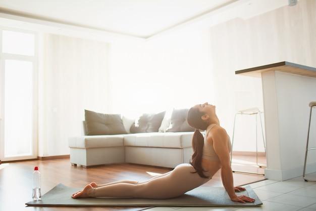 Jovem mulher a fazer exercícios de ioga na sala durante a quarentena. garota fazendo pose de cachorro virada para cima. alongamento para trás e parte superior do corpo em casa na esteira.