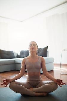 Jovem mulher a fazer exercícios de ioga na sala durante a quarentena. menina sente-se em posição de lótus e medite com os olhos fechados. alongamento e exercícios em casa.