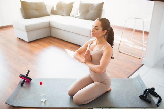 Jovem mulher a fazer exercícios de ioga na sala. vista para cima se a menina juntos de mãos dadas na posição de jogar. sente-se no tapete e medite após o treino esportivo.
