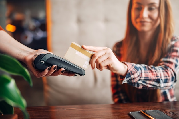 Jovem mulher a pagar pelo telemóvel num café