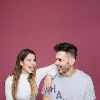 Jovem mulher a sorrir com a mão no ombro do homem, mostrando as línguas