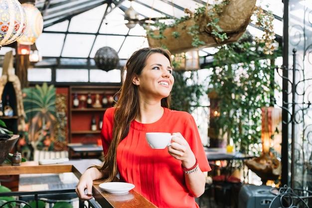 Jovem mulher a sorrir com café no café