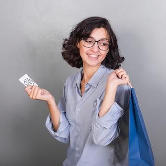 Jovem mulher a sorrir com cartão e sacola de compras