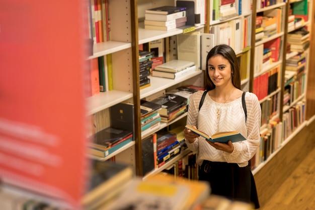 Jovem mulher a sorrir com livro perto da estante