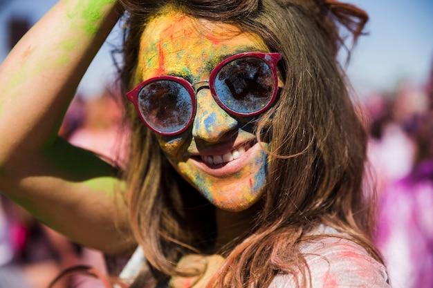Jovem mulher a sorrir com pó de holi no rosto com óculos de sol