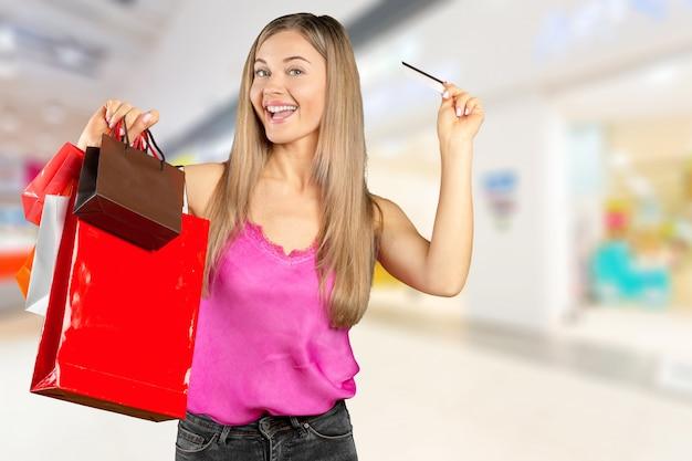 Jovem mulher a sorrir com sacos de compras sobre fundo de shopping
