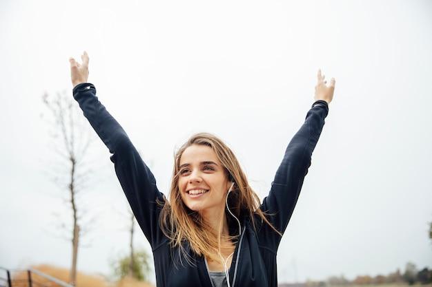 Jovem mulher a sorrir com smartphone e fones de ouvido, ouvindo música