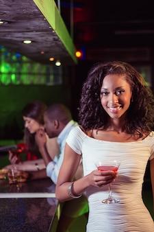 Jovem mulher a tomar um cocktail no balcão de bar em bar