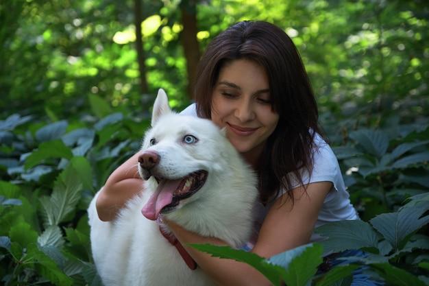 Jovem mulher abraçando e tocando seu cachorro