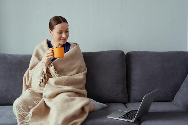 Jovem mulher abraçando em um cobertor quente com um laptop e uma xícara de chá