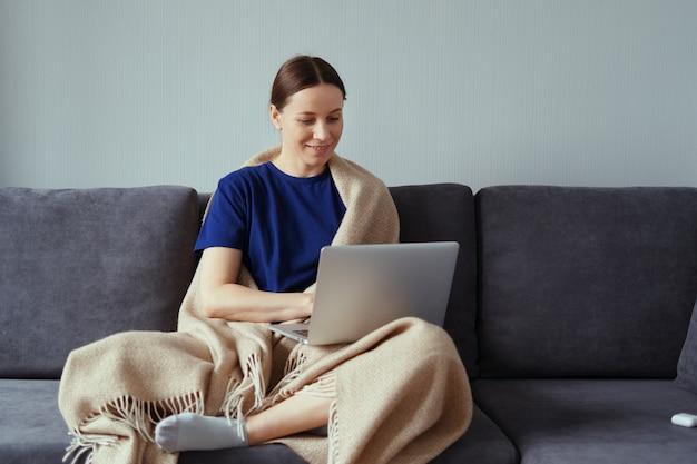 Jovem mulher abraçando em um cobertor quente com um laptop