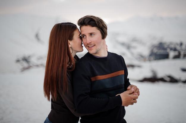 Jovem mulher abraçando o namorado de volta na montanha de neve