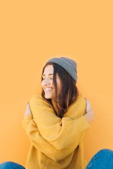 Jovem mulher abraçando-se com os olhos fechados
