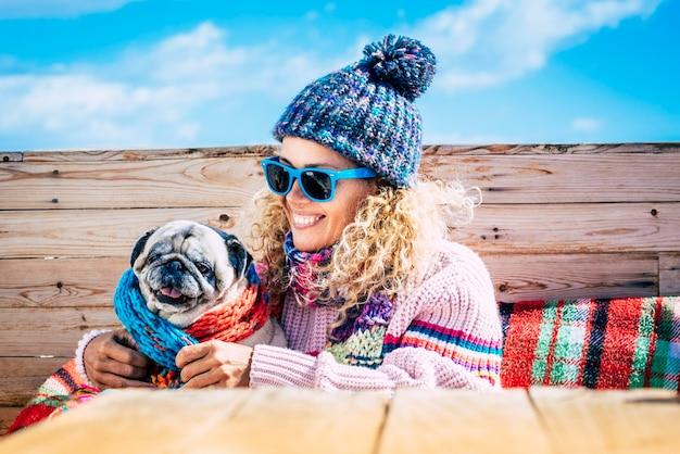Jovem mulher abraçando seu cachorro de estimação enquanto relaxa na cama contra o céu. perto da mulher e seu cachorro pug com roupas de inverno. mulher feliz com animal de estimação, aproveitando o inverno contra o céu.