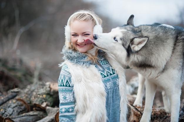 Jovem mulher abraçando seu cão husky
