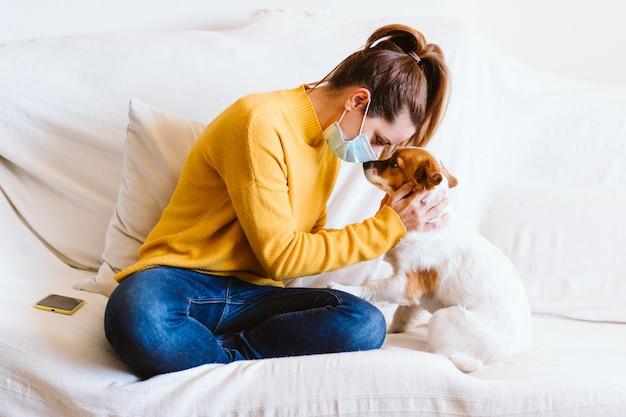 Jovem mulher abraçando seu cão pequeno bonito em casa, sentado no sofá, usando máscara protetora. fique em casa conceito durante o coronavírus covid-2019