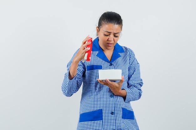 Jovem mulher abrindo a caixa de presente com camisa de pijama azul guingão e parecendo surpresa. vista frontal.