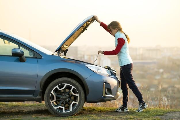 Jovem mulher abrindo o capô de um carro quebrado, tendo problemas com seu veículo.