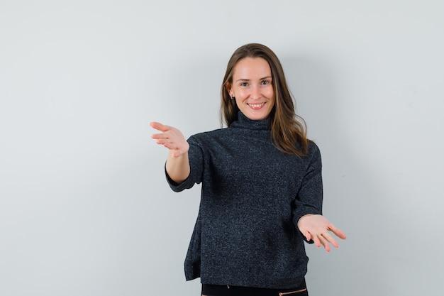 Jovem mulher abrindo os braços para um abraço na camisa e parecendo feliz. vista frontal.