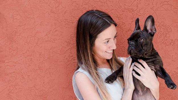 Jovem mulher acariciando seu bulldog francês