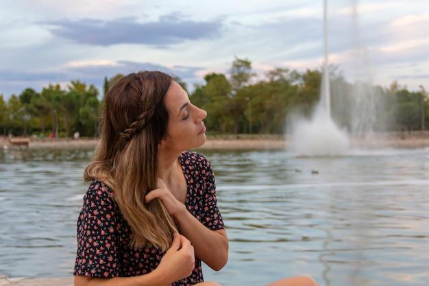 Jovem mulher acariciando seu cabelo em um lago com um fluxo de água. foco seletivo.