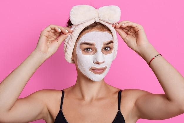 Jovem mulher adorável fazendo cuidados de saúde de beleza isolados sobre fundo rosa, mantendo as mãos na fita para o cabelo, olhando diretamente para a câmera, vestindo camiseta sem mangas.