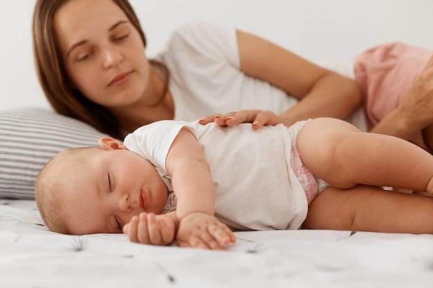 Jovem mulher adulta com cabelos escuros deitada com o bebê na cama, olhando para a filha para vê-la dormindo ou não, mulher vestindo camiseta branca casual, maternidade feliz.