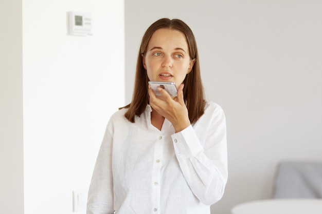 Jovem mulher adulta com cabelos escuros e aparência agradável, vestindo camisa branca estilo casual, olhando para longe, posando em uma sala iluminada em casa, gravando mensagem de voz ou comando.