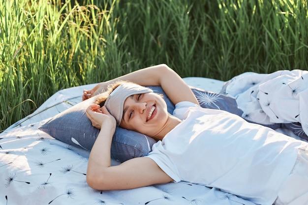 Jovem mulher adulta com sorriso dentuço deitado na cama macia no meio do campo com a venda nos olhos, olhando para a câmera com expressão facial feliz, descansando na natureza, verão.