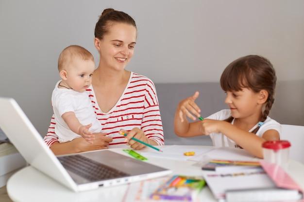 Jovem mulher adulta vestindo camisa listrada, segurando o bebê nas mãos e ajudando a filha mais velha a fazer a lição de casa, passando um tempo juntas, tendo uma expressão positiva e feliz.