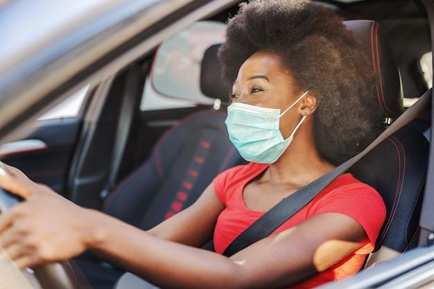Jovem mulher africana atraente com máscara no rosto, dirigindo o carro dela durante a pandemia covid-19.