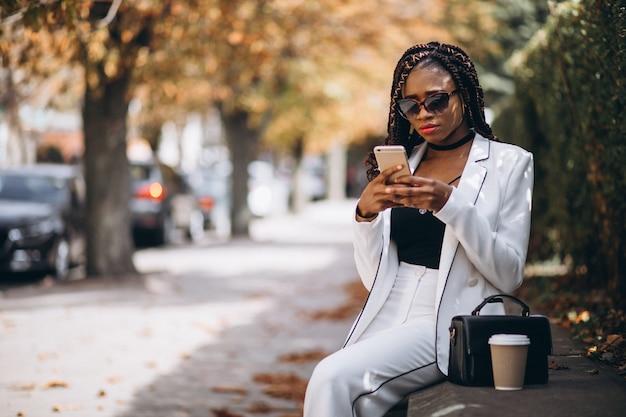 Jovem mulher africana, bebendo café e usando o telefone